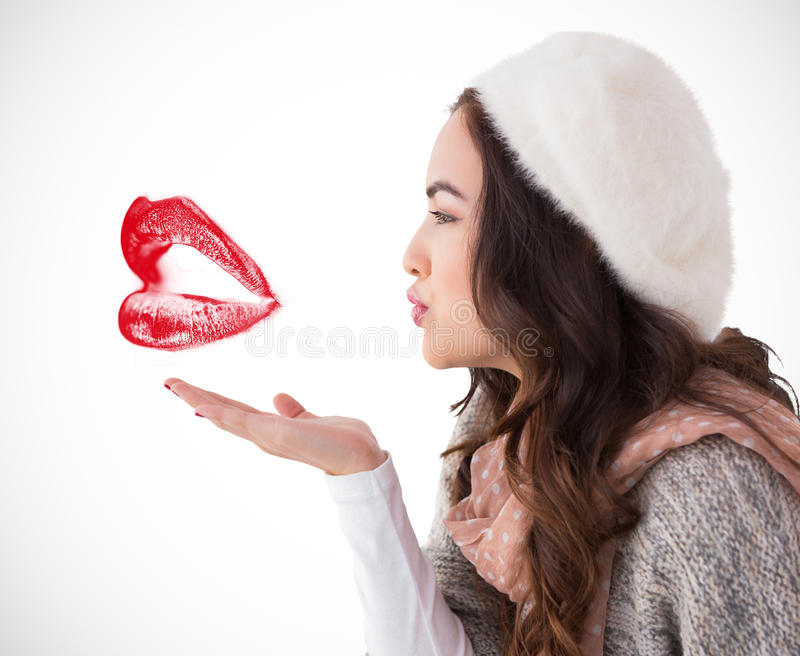 Het samengestelde beeld van brunette in de winter kleedt blazende kus royalty-vrije stock foto's