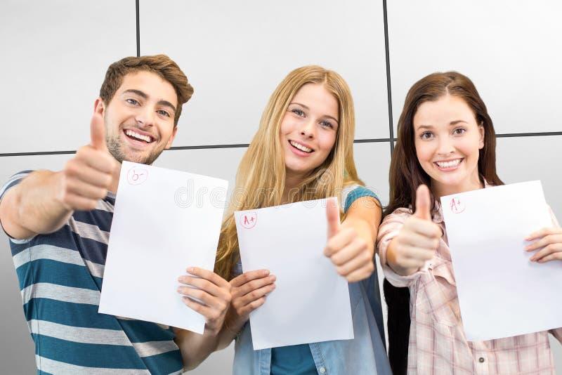 Het samengestelde beeld van examen steunen en studenten die beduimelt omhoog doen stock foto's