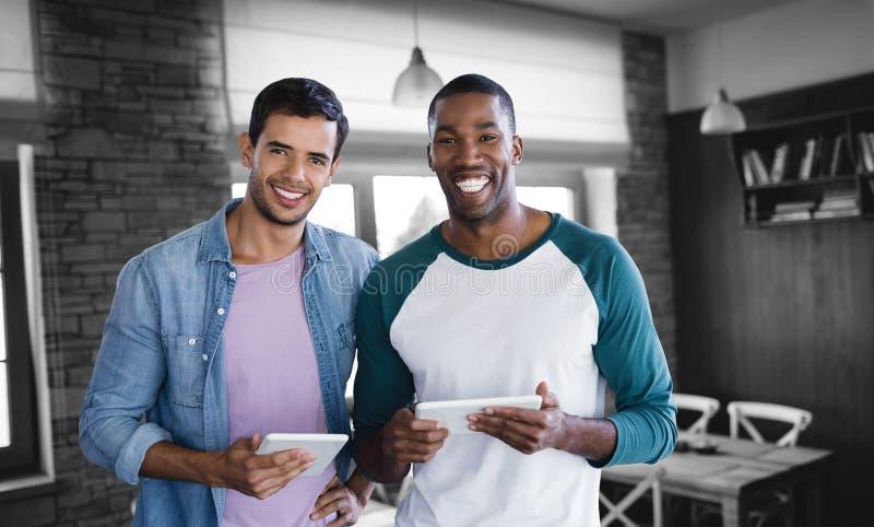 Het samengestelde beeld van glimlachende zakenlieden gebruikt een digitale tablet royalty-vrije stock afbeeldingen