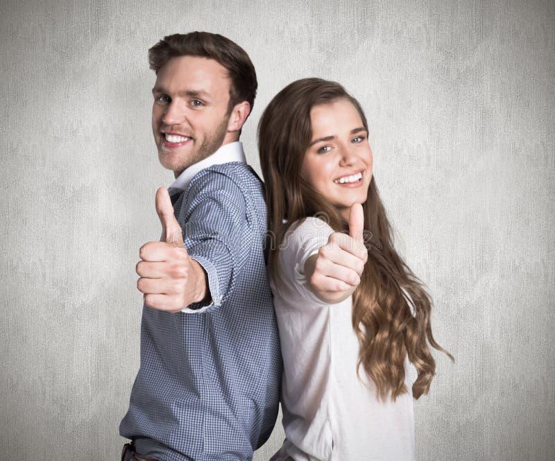 Het samengestelde beeld van het gelukkige jonge paar gesturing beduimelt omhoog royalty-vrije stock afbeelding