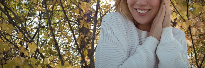 Het samengestelde beeld van portret van glimlachende vrouw die sweater met handen dragen clasped stock fotografie