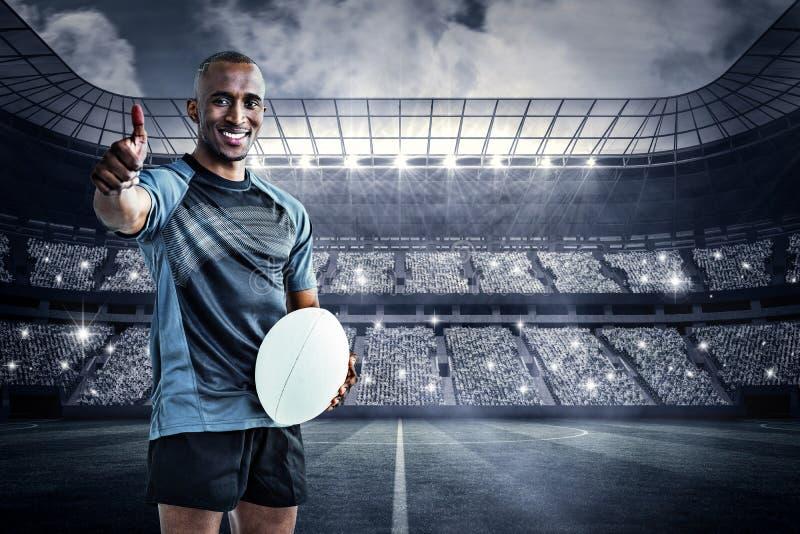 Het samengestelde beeld van portret van het zekere rugbyspeler glimlachen en het tonen beduimelt omhoog stock foto