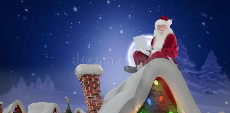 Het samengestelde beeld van santa zit en gebruikt laptop stock afbeelding