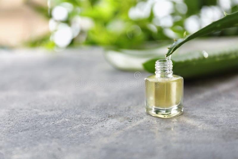 Het sap die van aloëvera van groen blad in fles op grijze lijst druipen stock fotografie