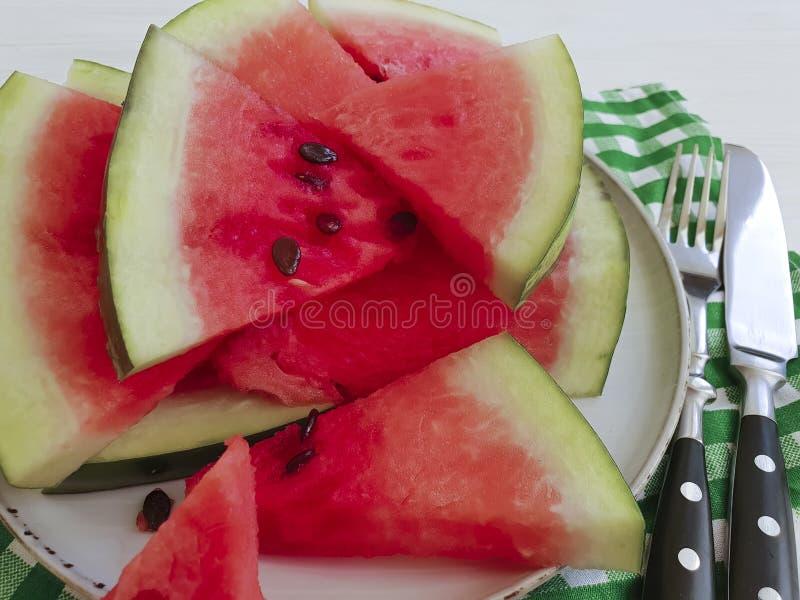 Het sappige middel tegen oxidatie van de het fruit zoete zomer van watermeloenstukken van een plaatservet op een witte houten ach stock afbeelding