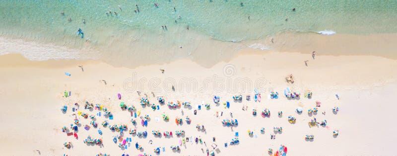 Het satellietbeeld overbevolkte openbaar strand met kleurrijke paraplu's, Satellietbeeld van zandig strand met toeristen die in m royalty-vrije stock foto's