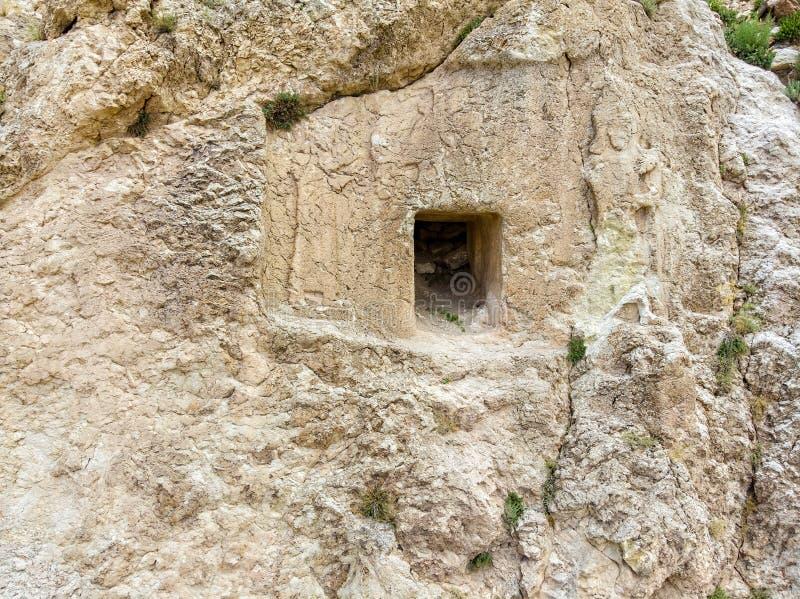 Het satellietbeeld van bas-hulp sneed in de rots die het ingangskader van een huis versiert dat in de rots wordt gesneden Oosteli royalty-vrije stock foto's
