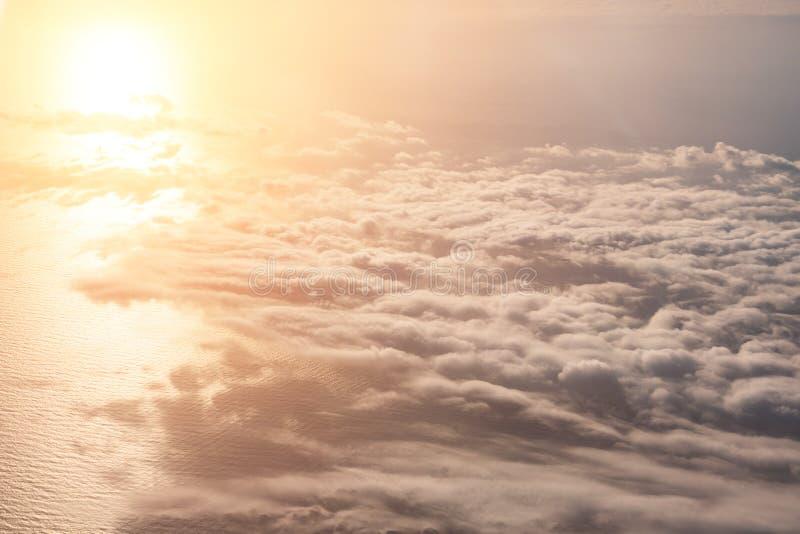 Het satellietbeeld van de hoogte van de vlucht boven de wolken, wordt de zon weerspiegeld in de spiegeloppervlakte van het overze royalty-vrije stock afbeeldingen