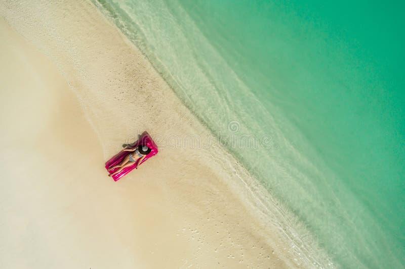 Het satellietbeeld van het slanke vrouw zwemmen op zwemt matras in het transparante turkooise overzees De zomerzeegezicht met moo royalty-vrije stock foto