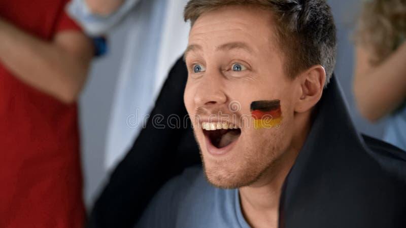 Het scanderende en ondersteunende team van de emotionele Duitse voetbalventilator, het letten op spel op TV royalty-vrije stock afbeeldingen