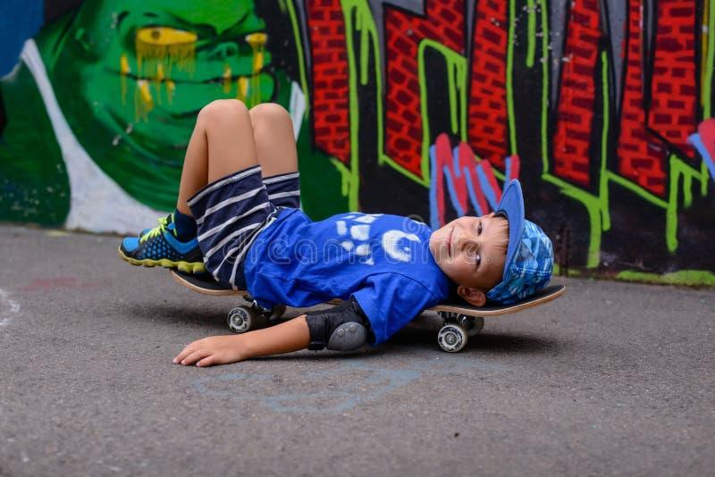 Het schelmse jonge jongen ontspannen op zijn skateboard stock foto's