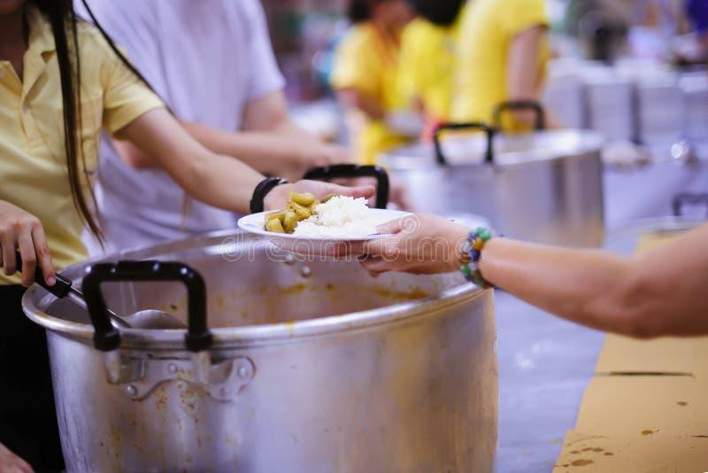 Het schenken van voedsel aan bedelaars om honger te verminderen: het concept het delen van hulp aan mede menselijke wezens in de  stock afbeelding