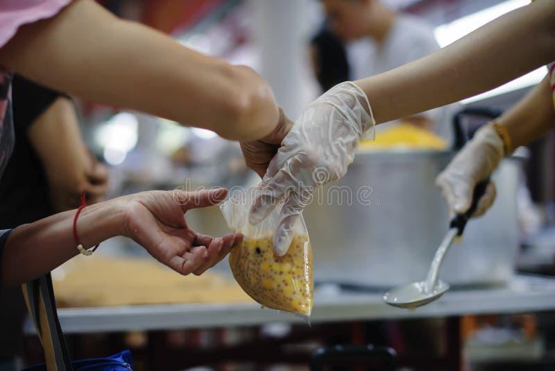 Het schenken van voedsel aan bedelaars om honger te verminderen: het concept het delen van hulp aan mede menselijke wezens in de  royalty-vrije stock afbeelding