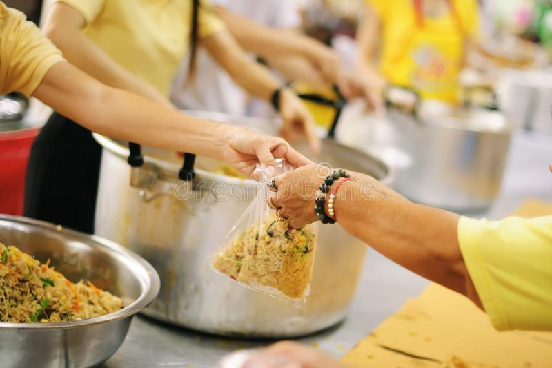 Het schenken van voedsel aan bedelaars om honger te verminderen: het concept het delen van hulp aan mede menselijke wezens in de  royalty-vrije stock afbeeldingen