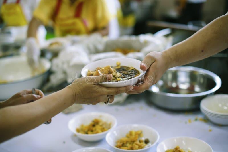 Het schenken van voedsel aan bedelaars om honger te verminderen: het concept het delen van hulp aan mede menselijke wezens in de  stock foto