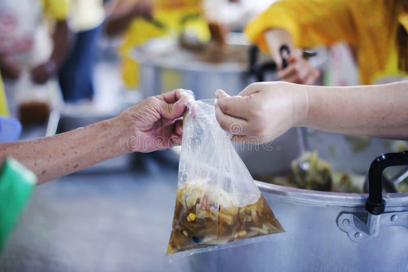 Het schenken van voedsel aan bedelaars om honger te verminderen: het concept het delen van hulp aan mede menselijke wezens in de  stock afbeeldingen
