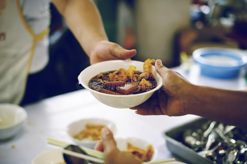 Het schenken van voedsel aan bedelaars om honger te verminderen: het concept het delen van hulp aan mede menselijke wezens in de  stock fotografie