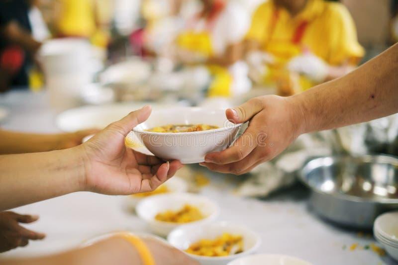 Het schenken van voedsel aan bedelaars om honger te verminderen: het concept het delen van hulp aan mede menselijke wezens in de  royalty-vrije stock fotografie
