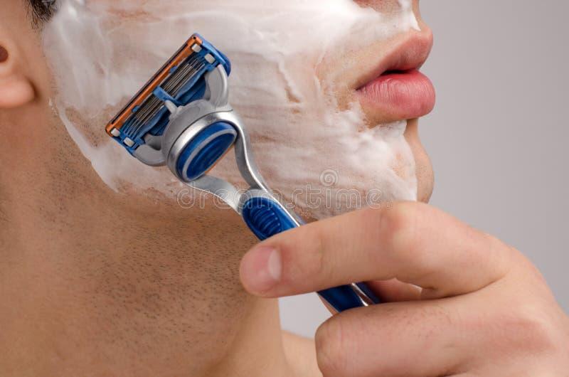 Het scheren van de baard met een scheermes. stock foto