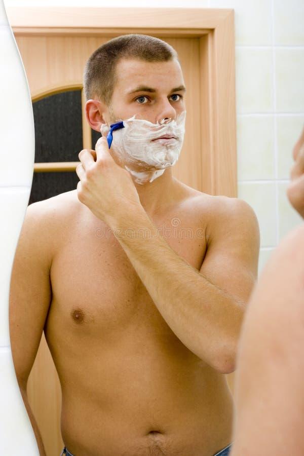 Het scheren van de jonge mens in de spiegel van de badkamers stock afbeelding