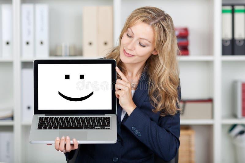 Het Scherm van onderneemsterDisplaying Smiley Face On Laptop stock foto's