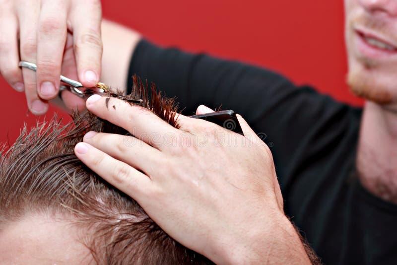 Het scherpe haar van de kapper op de jonge mens
