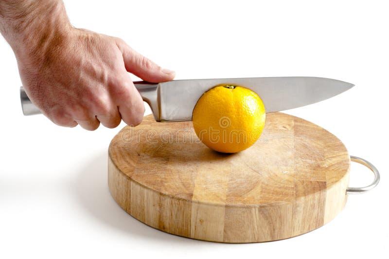 Het scherpe knipsel van het roestvrij staalmes in sinaasappel royalty-vrije stock foto's