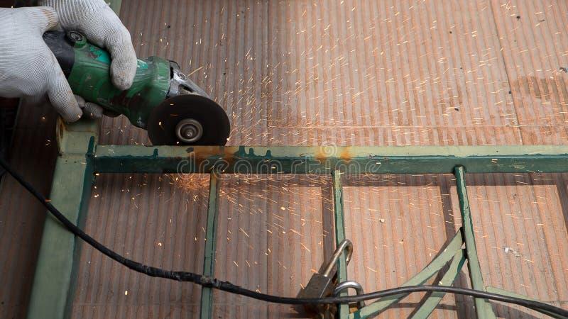 Het scherpe metaal van de arbeider met molen royalty-vrije stock fotografie
