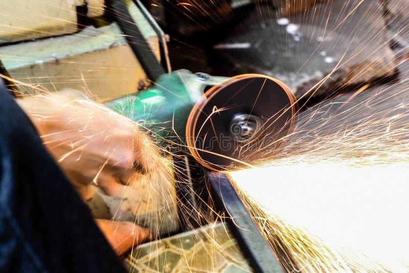 Het scherpe metaal van de arbeider met molen Vonkt terwijl het malen van ijzer stock afbeelding