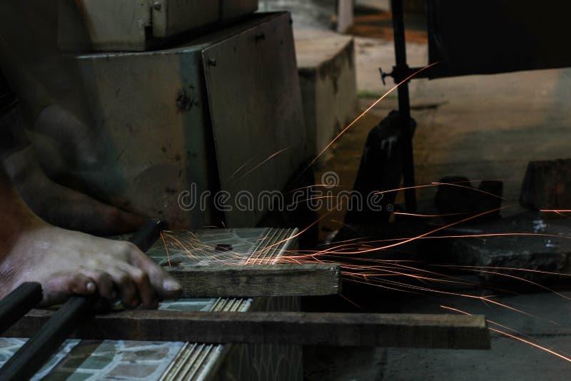 Het scherpe metaal van de arbeider met molen Vonkt terwijl het malen van ijzer stock foto's