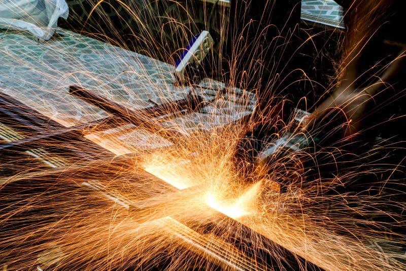 Het scherpe metaal van de arbeider met molen Vonkt terwijl het malen van ijzer stock fotografie