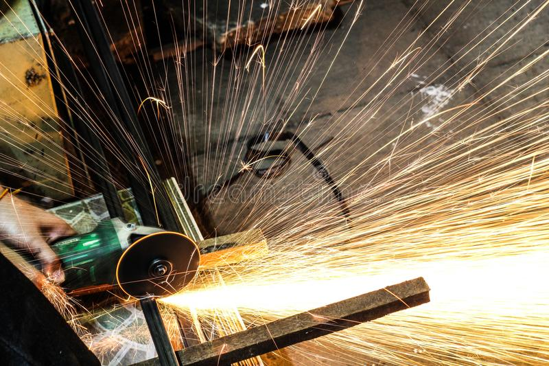 Het scherpe metaal van de arbeider met molen Vonkt terwijl het malen van ijzer royalty-vrije stock foto