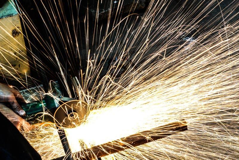 Het scherpe metaal van de arbeider met molen Vonkt terwijl het malen van ijzer stock afbeeldingen