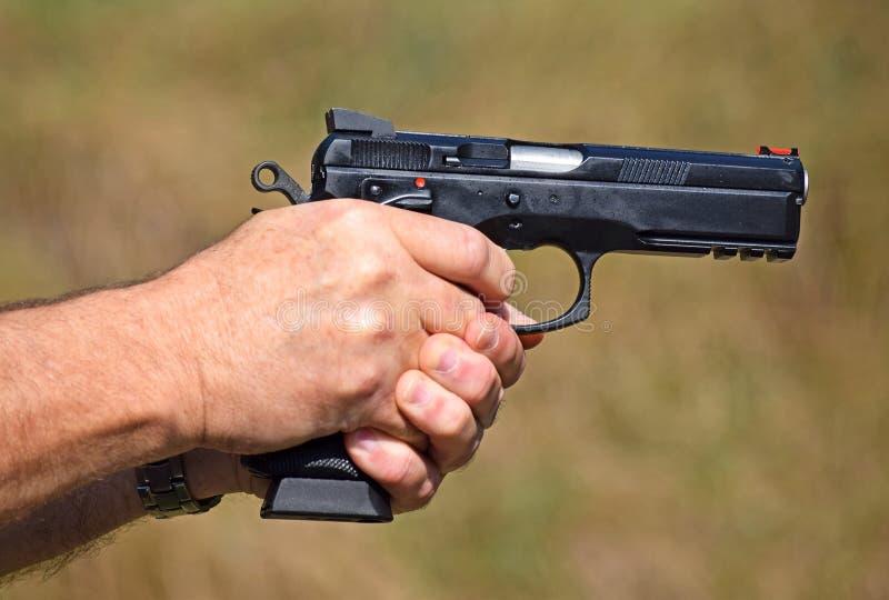 Het schieten met een pistool royalty-vrije stock afbeeldingen