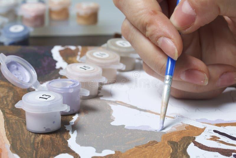 Het schilderen op canvas door aantallen Een vrouw houdt een borstel en trekt het Genummerde containers met verven en borstels op  royalty-vrije stock afbeeldingen