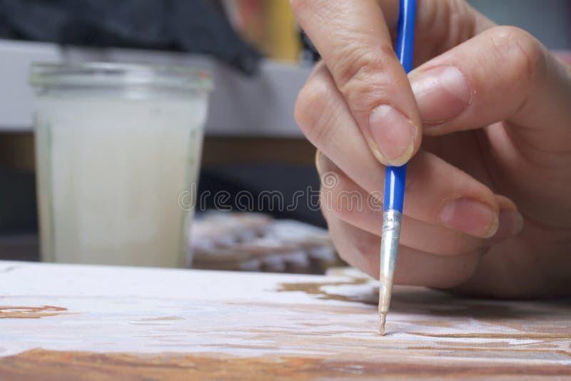 Het schilderen op canvas door aantallen Een vrouw houdt een borstel en trekt het Genummerde containers met verven en borstels op  stock fotografie