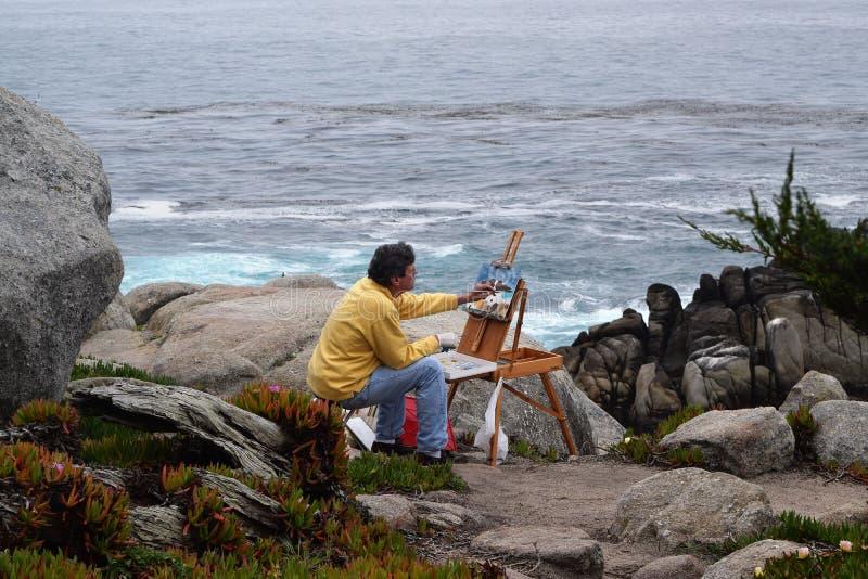 Het schilderen op rotsen van het overzeese canvas schilderen schildersezel stock foto