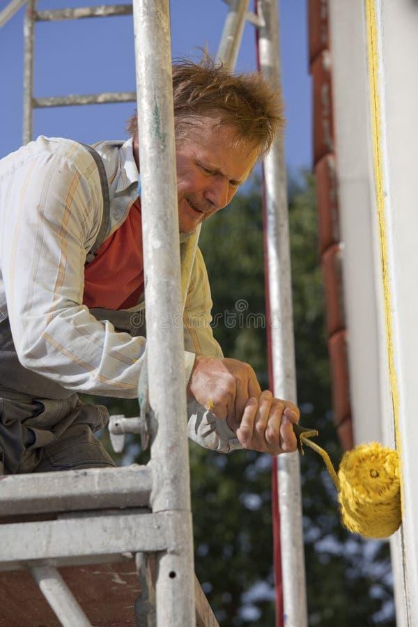 Het schilderen van de arbeider huis met rol stock fotografie