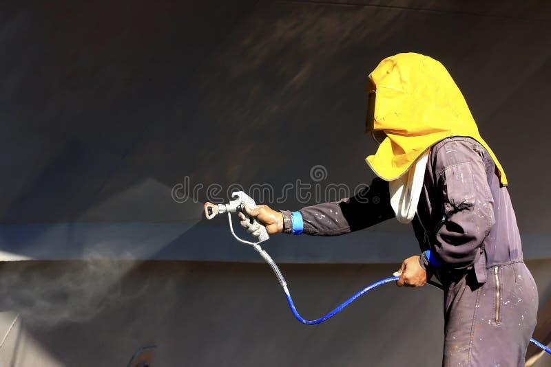 Het schilderen van de arbeider schipschil die luchtpenseel met behulp van royalty-vrije stock fotografie