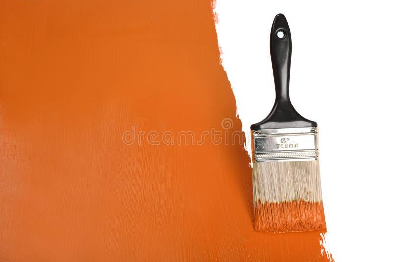 Het Schilderen van de borstel Muur met Oranje Verf stock afbeeldingen