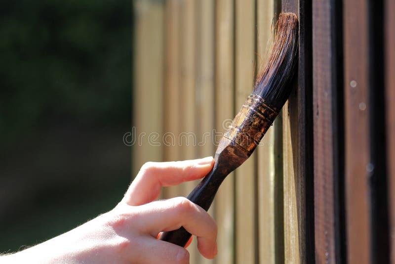 Het schilderen van de houten tuinomheining royalty-vrije stock afbeeldingen