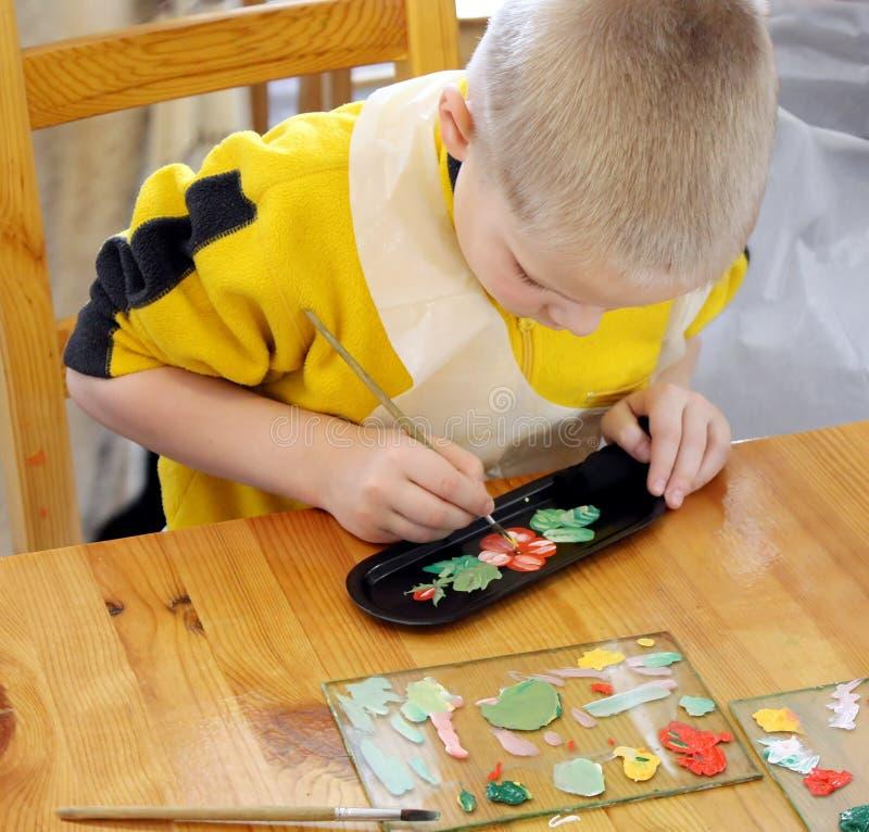 Het schilderen van de jongen plaat stock afbeelding
