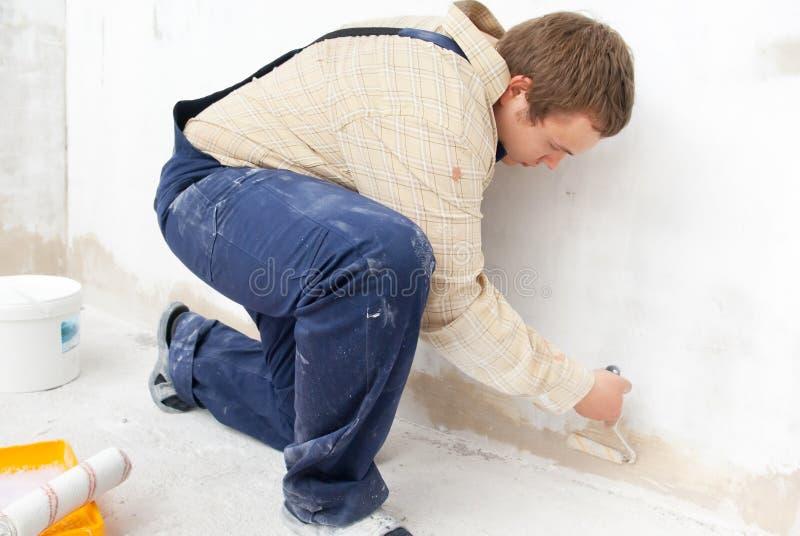 Het schilderen van de mens muur met kleine rol stock fotografie