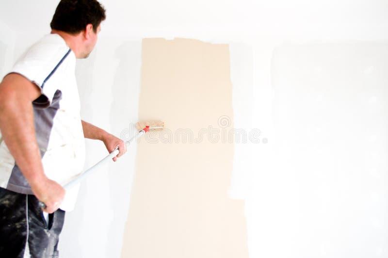 Het schilderen van de schilder muur thuis stock foto