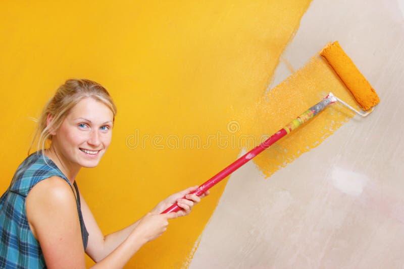 Het schilderen van de vrouw muur stock afbeeldingen