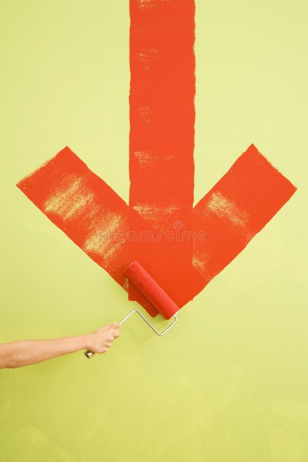 Het schilderen van de vrouw pijl op muur. stock foto