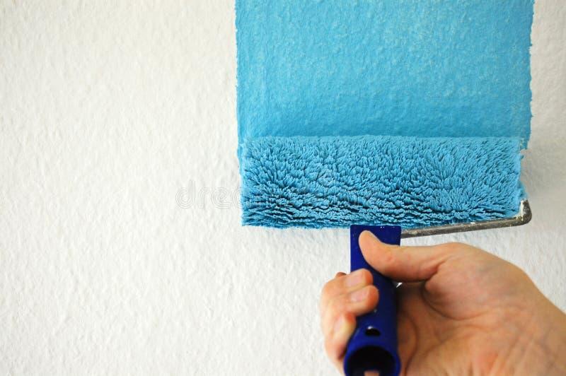 Het schilderen van een muur met blauwe verf stock afbeeldingen