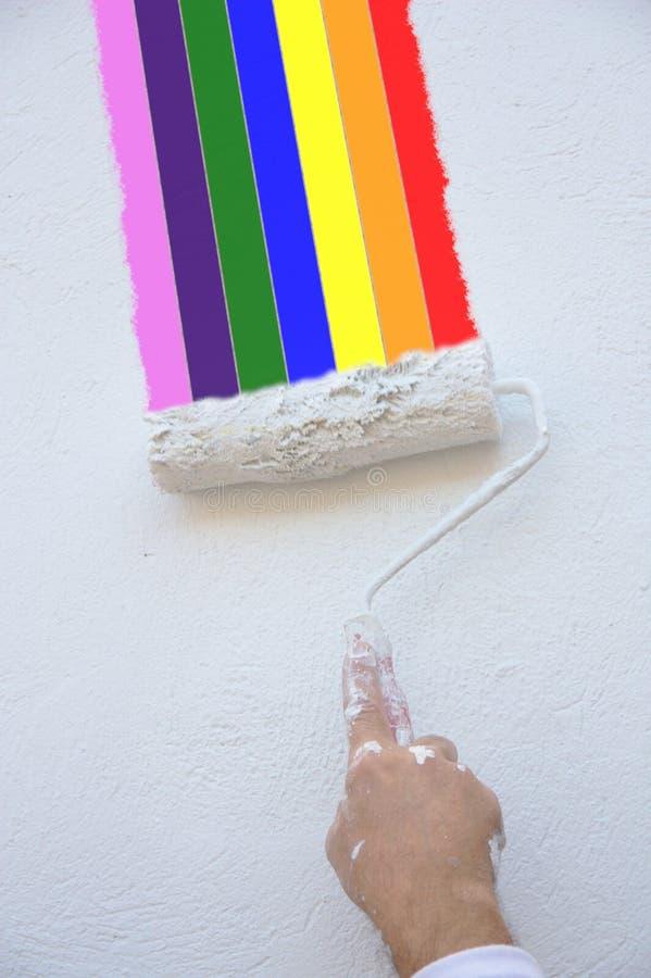 Het schilderen van een regenboog op een blinde muur met de rol van een schilder stock afbeelding