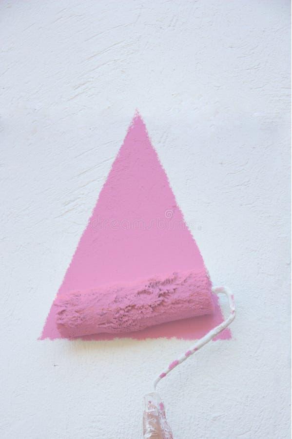 Het schilderen van een roze driehoek op een witte muur stock fotografie
