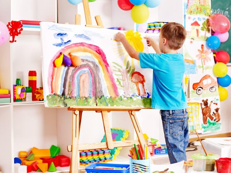 Het schilderen van het kind bij schildersezel. stock foto's